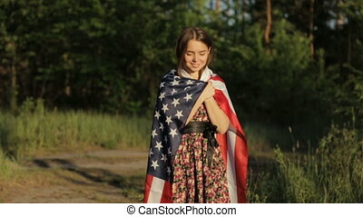 Girl at sunset with American flag in hands - Beautiful woman...