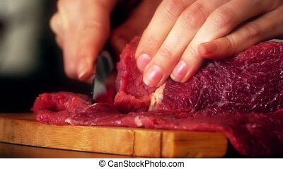 Woman cuts raw beef on the wooden cutting board. 4K close-up...