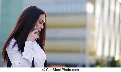 Slow motion shot of a young businesswoman talking over a phone