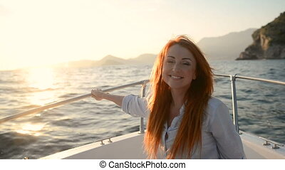 young happy woman sitting in going cutter looks at adriatic sea