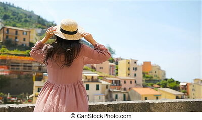 Young woman with beautiful view at old village Riomaggiore,...