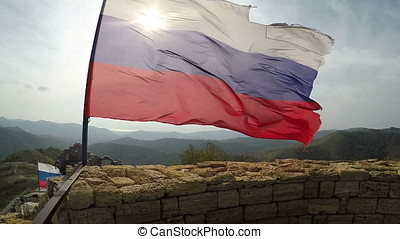 Ragged Russian flag fluttering on wind in fortress ruins