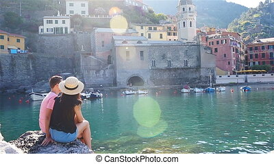 Young couple in a cove on a rock in the Cinque Terre...