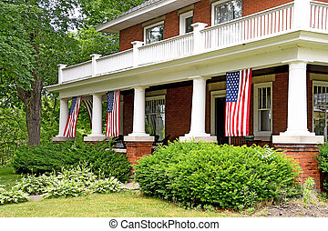 old brick home with American flags - hanging American flags...