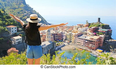 Young woman with great view at old village Vernazza, Cinque...