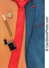 Denim jacket, cufflink, cigar and lighter lying on a wooden...