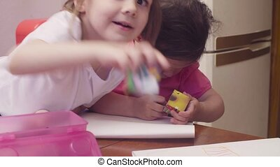 Two little girls drawing at a table