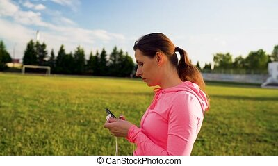 Woman inserts headphones into ears, preparing for a run at...