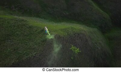 Woman tourist stands on top of a hill and waving with a...