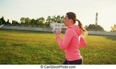 Woman with headphones and smartphone runs through the...