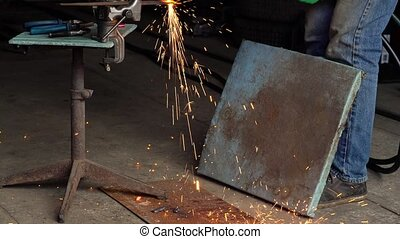 Worker cuts the metal with a retro cutter in a small...