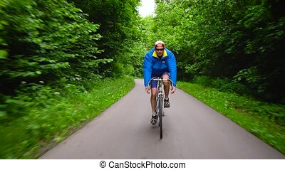 Middle-aged man is riding a road bike along a forest road....