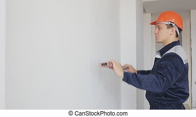 man using a spirit level to check wall indoor