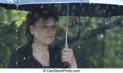 Woman under umbrella at rain - Sad woman under umbrella at...