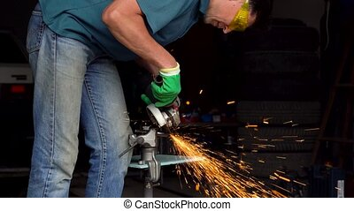 Male-middle-aged worker with angular grinding machine is...