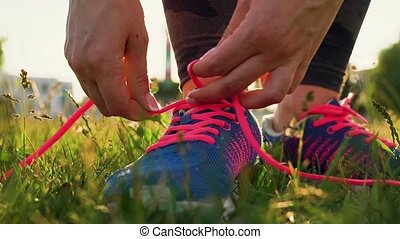 Running shoes - woman tying shoe laces. Slow motion -...