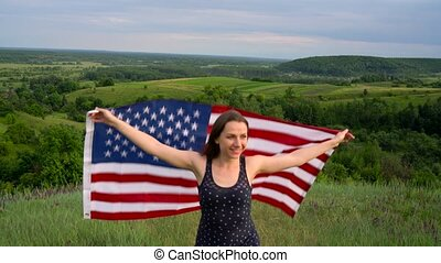 Woman waving a US flag is standing on top of a hill - the concept of Independence Day USA