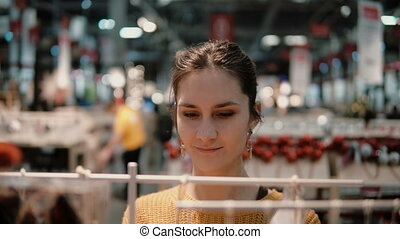 Attractive happy young woman chooses at store some goods....