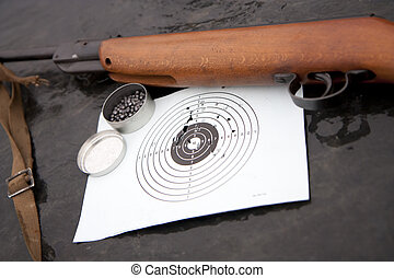 Air guns and a target with holes