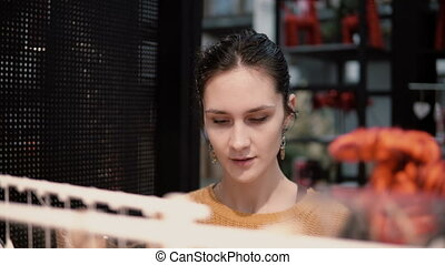 Attractive happy young woman chooses at store some goods on shelves. decor for home interior