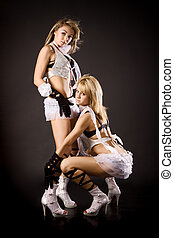 two beautiful dancer girl in white costumes on black...