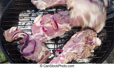 BBQ with meat steaks - grilling meat, placing raw meat on...