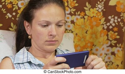 A young woman is checking messages on a mobile phone at home on the couch.