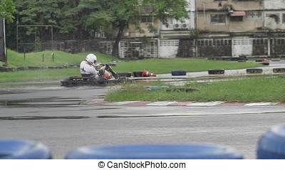 Karting - driver in helmet on kart circuit. Adult Kart Racer on Track. Rainy weather on the race track. Slow motion