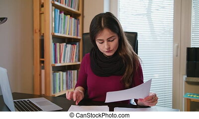 Serious Young Woman Looking on Documents.