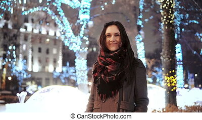 attractive woman at snowy Christmas night smiles looking at the camera in front of park trees decorated sparkling lights