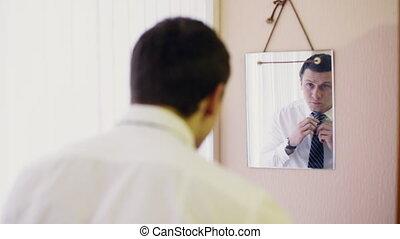 man ties up tie in front of mirror