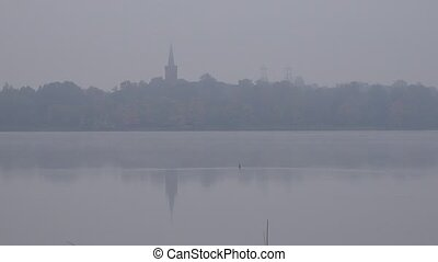 Church tower on lake shore in dense fog in autumn morning. Zoom out. 4K