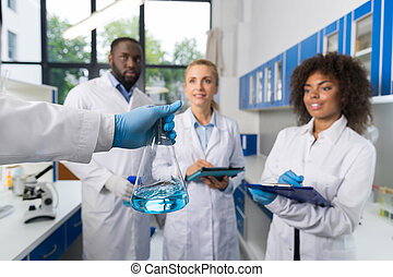 Scientist Holding Flask With Group Of Students Taking Notes Making Research In Laboratory, Mix Race Team Of Doctors Writing Results Of Experiment
