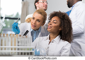 Two Female Scientist Examine Sample Working In Modern...