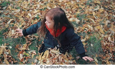 point of view cute little girl playing in the autumn park, sits on grass throws up yellow fallen leaves 4k
