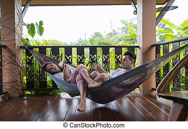 Young Couple Lying In Hammock On Terrace Tropical Hotel, Man...