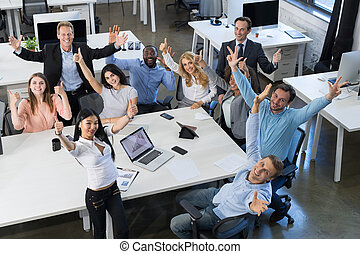 Successful Excited Mix Race Businesspeople Team Sitting At Table On Meeting, Holding Raised Hand Happy Smiling Business Man And Woman