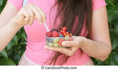 Close up of woman hands holding berries and fruits mix -...