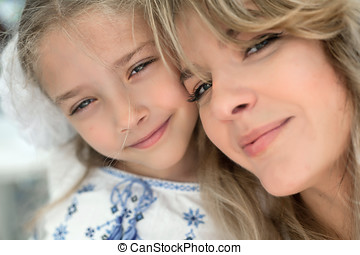 Close-up portrait of happy cheerful beautiful young mother with her little smiling daughter.