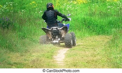 Unknown man wearing protective suit riding ATV or quad on a...