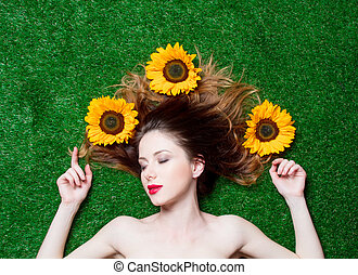 red-haired girl with sunflowers on grass - Portrait of...