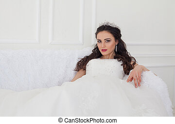 bride in a wedding dress and a crown sits in the white hall...