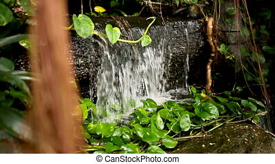 The water flows as a small decorative waterfall. Wat Saket...