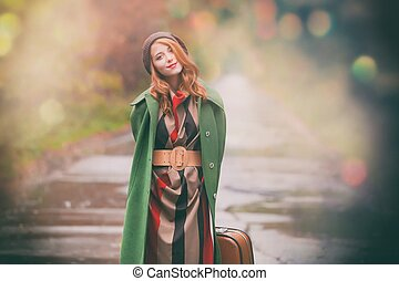 woman with suitcase in autumn park with bokeh - Portrait of...