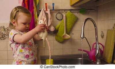 Little baby girl standing near kitchen sink with a toy mouse