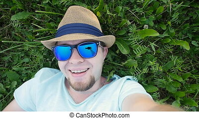Happy man is lying on a grass in a park taking selfie