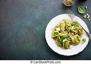 Homemade Italian tortelloni with green pesto, goat cheese...
