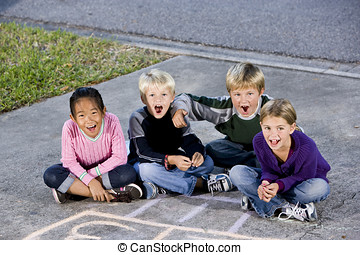Children sitting together laughing on driveway - Four kids...