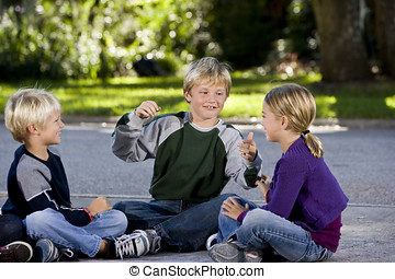 Children sitting and talking together on driveway - Three...