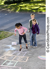 Kids playing hopscotch - Asian girl jumping on hopscotch...